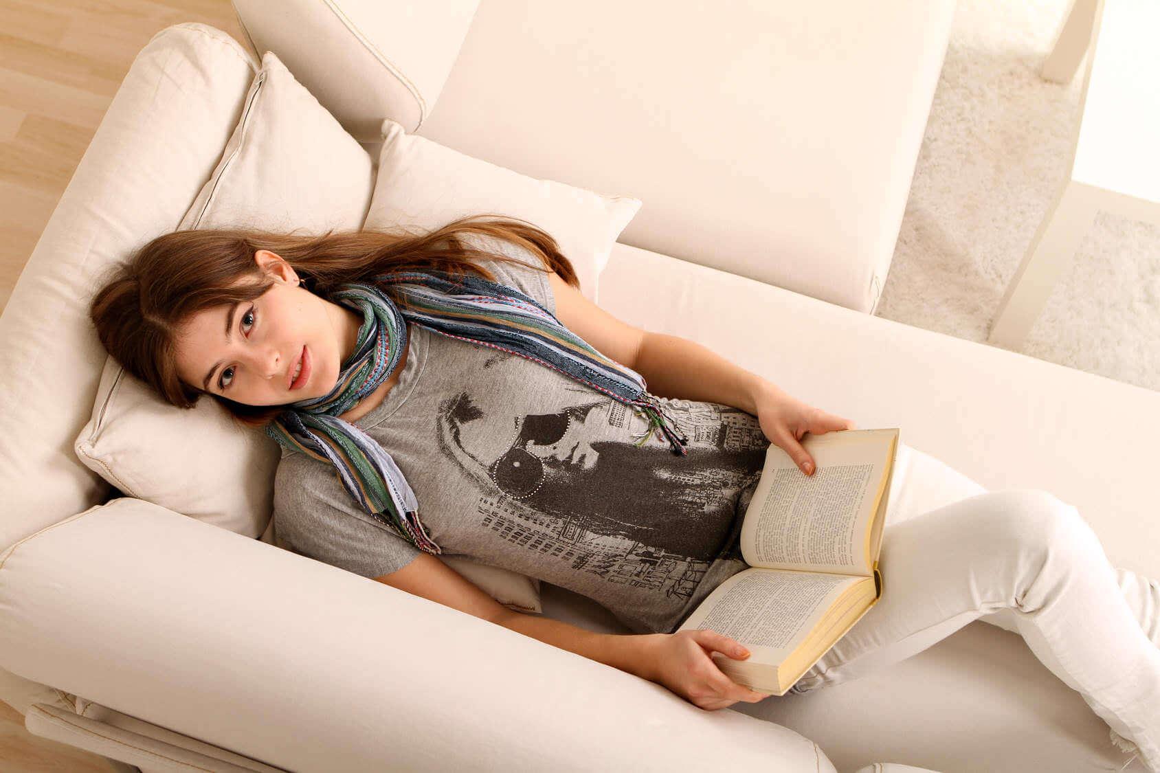 Jak robić dobre zdjecia - kobieta leżąca na kaniepie czyta książkę - kadr z góry
